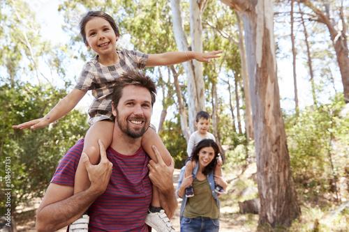 Fotografia  Children Riding On Parent's Shoulders On Countryside Walk