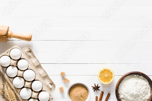 Fotobehang Koken Baking ingredients on white table. Box of white eggs, brown sugar, spices, lemon, white flour and rolling pin on white wooden table background. Top view and copy space