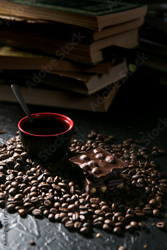 Photo Stands Coffee beans coffee cup and coffee beans and chocolate on the background of books