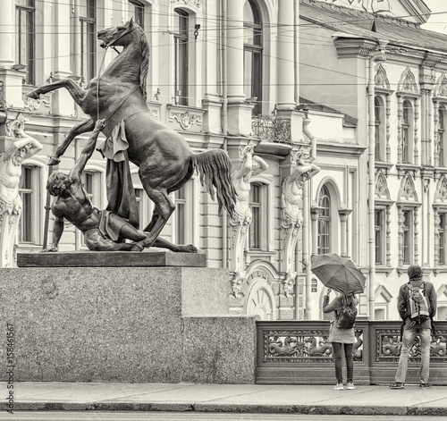 Photo Stands Music Band Horse Tamer statue on Anichkov bridge in Saint Petersburg.