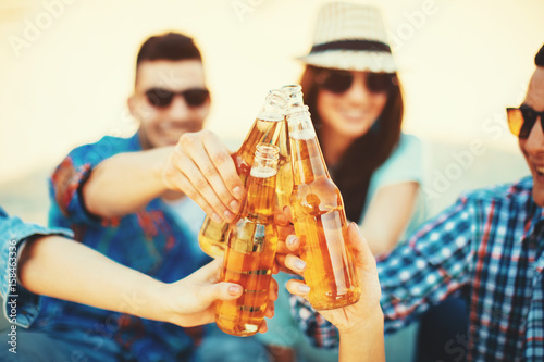 Happy young people having fun on the beach and drinking beer Poster