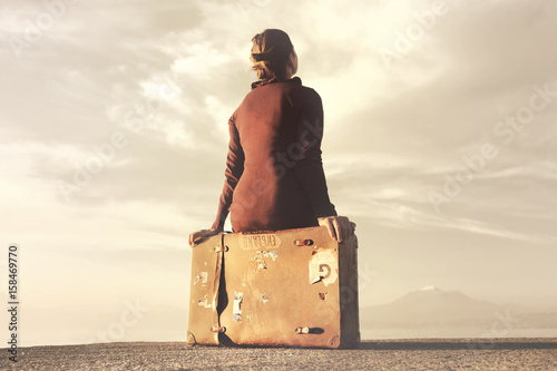 Fotografering Traveler woman arriving at destination relaxes sitting on her suitcase