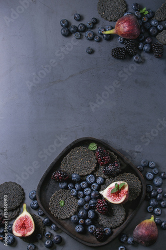 Fotografia, Obraz  Variety of fresh berries blueberry, dewberry, red currant and figs with black charcoal crackers on wooden plate over dark metal background