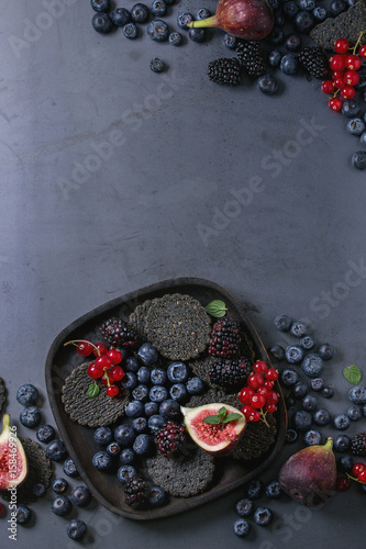 Fotografija  Variety of fresh berries blueberry, dewberry, red currant and figs with black charcoal crackers on wooden plate over dark metal background
