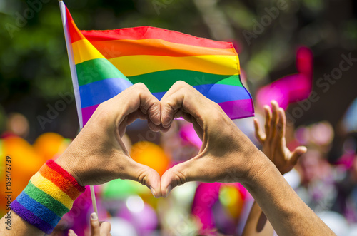 Fotografía  Supporting hands make heart sign and wave in front of a rainbow flag flying on t