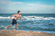 young muscular guy with a naked torso runs along the beach