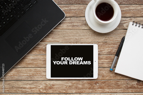 Tablet on desktop with follow your dreams text. Canvas Print