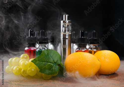 Electronic cigarette, lemons and bunch of grapes within vapor on black backgroun Wallpaper Mural