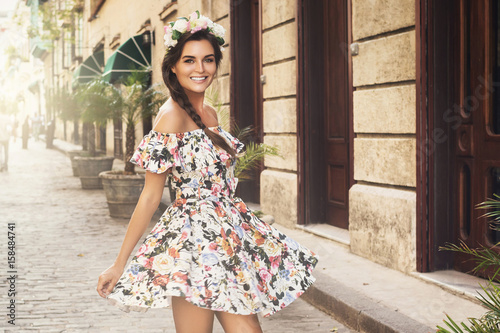 Leinwand Poster Happy woman in beautiful dress on the street