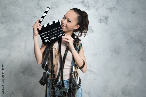 Smiling pretty teen woman with movie objects, clapper board and unrolled filmstrip