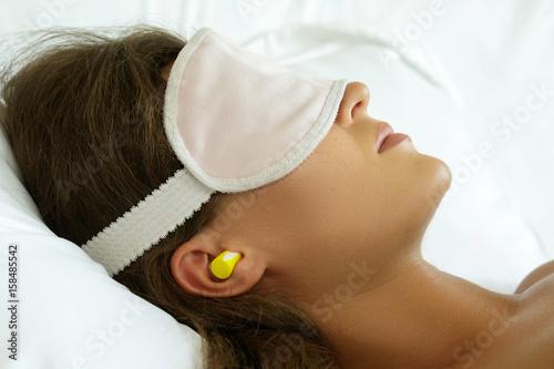 Fotografie, Obraz  Woman is wearing eye mask and using earplugs
