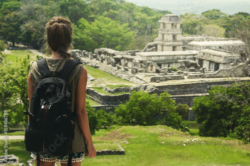 Obraz Woman with backpack beside ancient Mayan ruins - fototapety do salonu