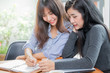 Young asian women working together, woman doing homework in modern place, woman working together with happy emotion concept.