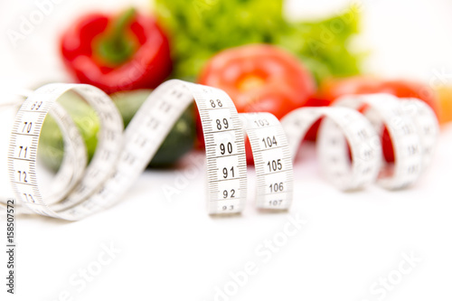 Fitness and healthy food diet concept. Fresh green vegetables, measuring tape isolated on white background. Closeup