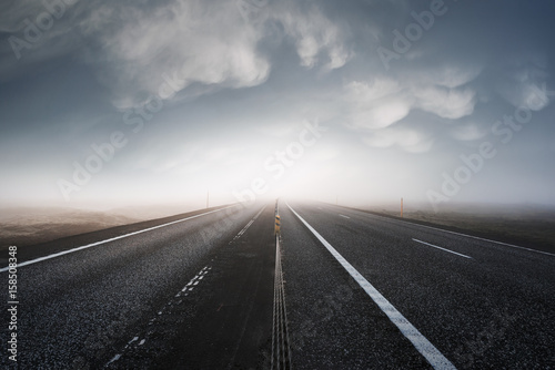 Poster Taupe Asphalt road leaving in a bright light