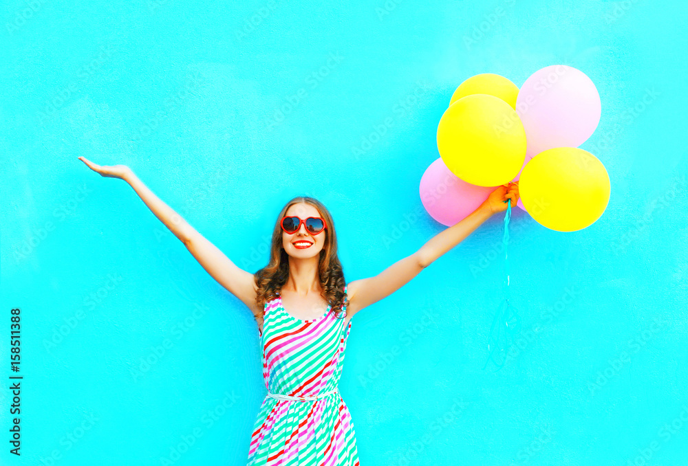 Fototapety, obrazy: happy smiling woman and an air colorful balloons is having fun on a blue background