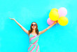 happy smiling woman and an air colorful balloons is having fun on a blue background