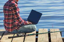 A Fisherman Man Works On A Laptop, Sits On A Wooden Pier Near The Lake, Next To It There Is A Fishing Pole.