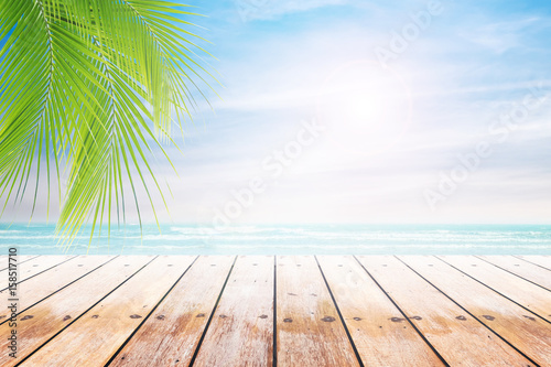 Foto auf Gartenposter Strand Empty wooden table and palm leaves with party on beach blurred background in summer time.