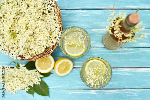 Obraz na plátně Two glasses of elderflower lemonade and bottle of homemade syrup, top view
