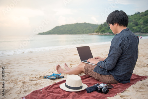 Fotografía Young Asian man working with laptop computer on tropical beach, digital nomad li