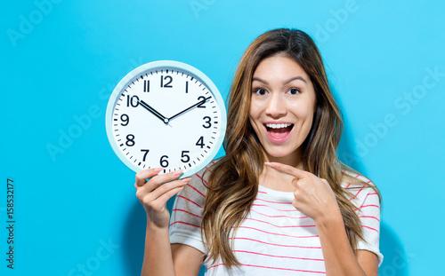 Obraz na plátně Young woman holding a clock
