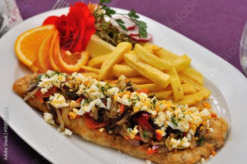 Fototapeta Filet rybny z warzywami i frytkami podany na białym owalnym talerzu