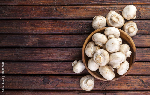 Top view of mushrooms champignon on wooden table. Copy space.