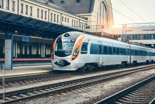 Fototapeta Wysoki prędkość pociąg przy stacją kolejową przy zmierzchem w Europa. Nowoczesny pociąg intercity na peronie kolejowym. Przemysłowy krajobraz z pociągiem pasażerskim na linii kolejowej. Transport kolejowy. Lokomotywa