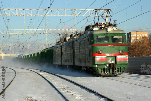 Photo  Freight train rides by rail in winter