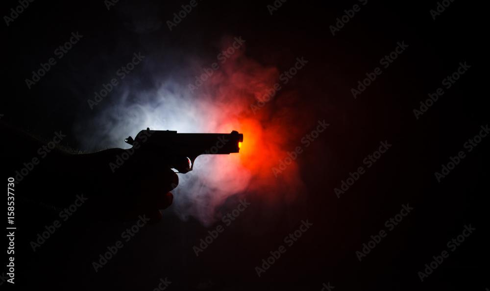 Fototapeta Male hand holding gun on black background with smoke ( yellow orange red white ) colored back lights, Mafia killer concept