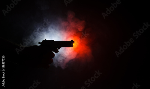 Fotografia Male hand holding gun on black background with smoke ( yellow orange red white )