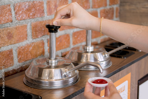 Woman's hand pumping the ketchup pump with brick wall pattern background Poster