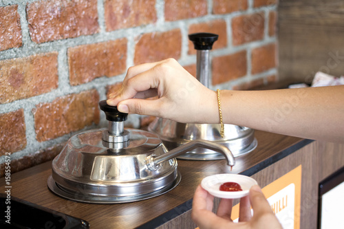 Photo  Woman's hand pumping the ketchup pump with brick wall pattern background