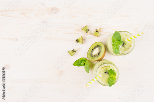 Foto op Canvas In het ijs Decorative frame of green kiwi fruit smoothie in glass jars with straw, mint leaf, cute ripe berry, top view. White wooden board background, copy space.
