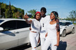 Three stylish african american friends making selfie on phone, wear on white clothes against two luxury cars. Street fashion of young black people. Black man with two african girls.