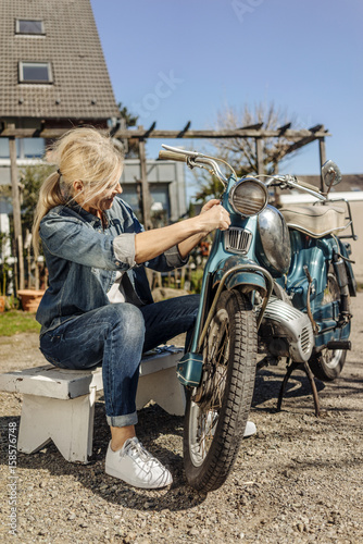Tuinposter Fiets Woman cleaning vintage motorcycle