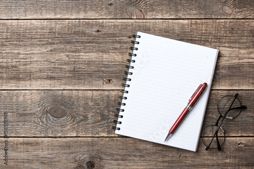 Notepad, pen and glasses on wooden desk Wallpaper Mural