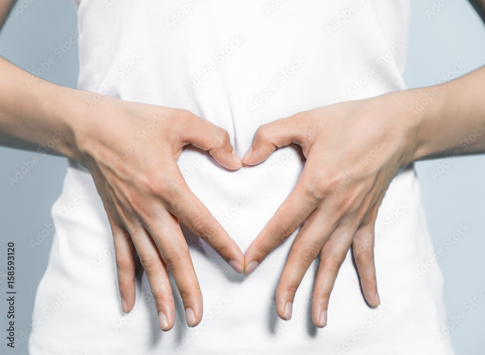 Fototapeta young woman who makes a heart shape by hands on her stomach.