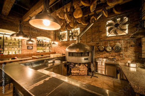 Rustic pizza oven, bar and kitchen in pizzeria interior