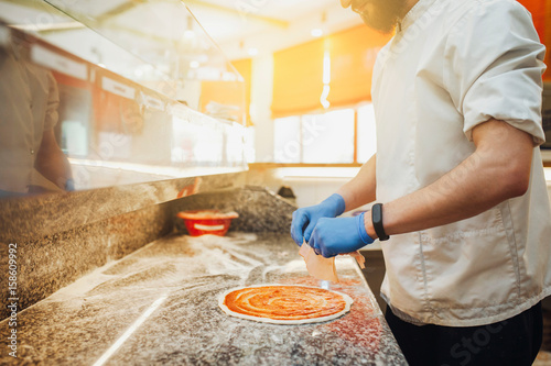 Chef starts to prepare pizza at a pizzeria