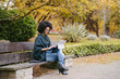 Stylish black female entrepreneur working with modern convertible laptop outdoor in autumn at city park. Young professional woman outside using tablet.