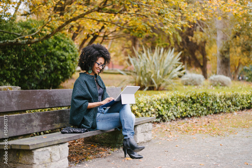 Foto  Stylish black female entrepreneur working with modern convertible laptop outdoor in autumn at city park
