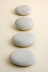 Fototapeta na wymiar Row of white zen stones on wooden mat, four pebbles in a row, massage and relaxation