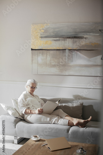 Pretty senior gray-haired Caucasian woman sitting on couch and reading a book.