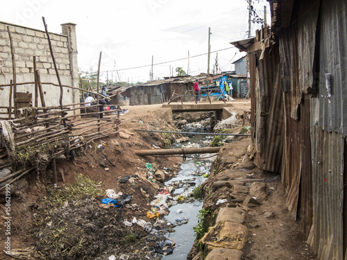 Staande foto Afrika Open sewer and tin shacks in a slum in Africa