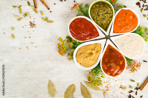 Fotografía  An assortment of sauces in a form of flower with spices on a light gray stone background