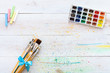 Paint brushes set and box with watercolors on white wooden stained table with splashes, artistic background for creative work, children kids easy painting art, back to school, top view, copy space