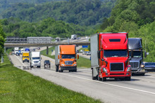 Flow Of Semis Lead The Way On A Busy Tennessee Highway.  Heat Waves Rising From The Pavement Give A Nice Effect To Vehicles And Forest Behind Lead Trucks.  Copy Space Across Top And Bottom Of Image.