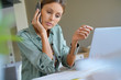 Woman working from home on laptop and talking on phone